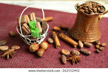 Still life with set of chocolate, spices and nuts on color mat , closeup - stock photo
