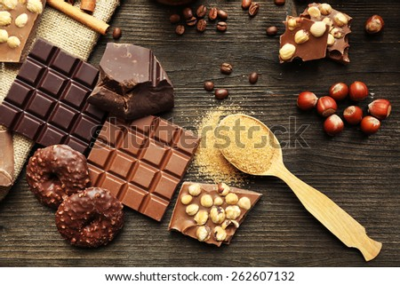 Still life with set of chocolate with nuts on wooden table, top view - stock photo