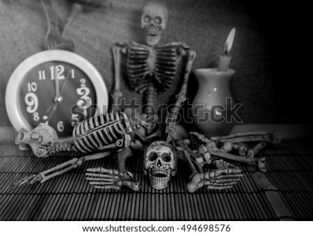 still life with skull skeleton clock and candle light