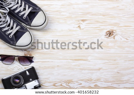 still life with sneakers, camera and sungalsses
