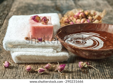 still life with spa towels and natural soap bar on wooden table - stock photo