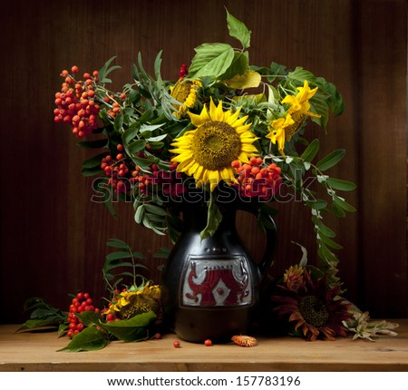 still life with sunflowers and mountain ash on a wooden background - stock photo