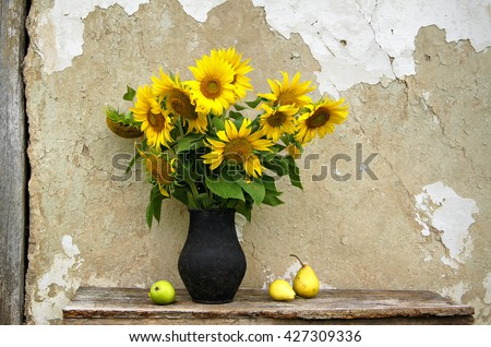 Still life with sunflowers and pears on the background of the old house wall - stock photo