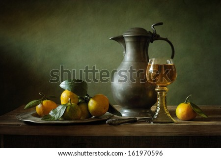 Still life with tangerines and a tin jar - stock photo