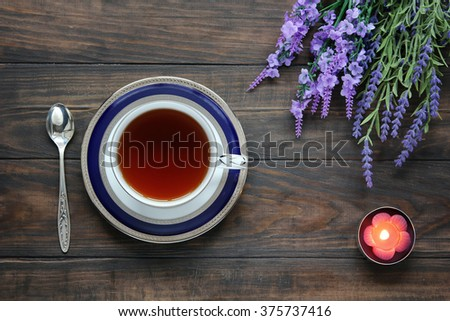 Still life with tea cup on saucer, lavender, silver tea spoon and aroma candle. Top view.  - stock photo
