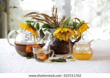 Still-life with tea in a transparent teapot, honey and sunflowers