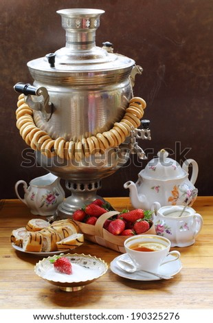 Still-life with the big samovar and fragrant fresh tea with a juicy lemon both an appetizing sweet batch and crackling small bagels and a fresh juicy ripe strawberry - stock photo