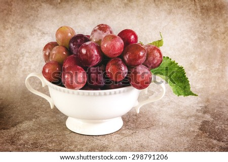 still life with the red grapes in white  vintage cup - stock photo