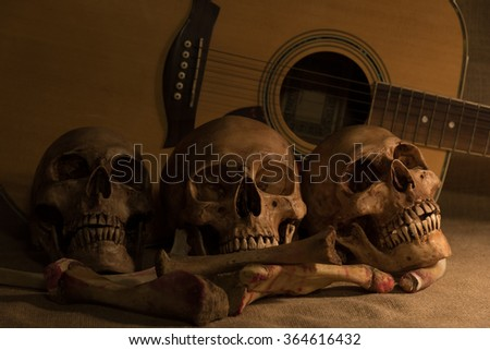 still life with three skulls, bones and guitar close up, dark concept