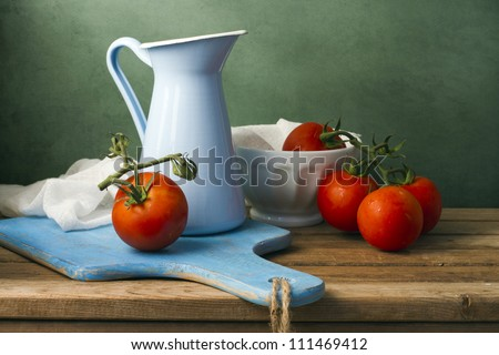 Still life with tomatoes and enamel jug. Arrangement on wooden table. - stock photo