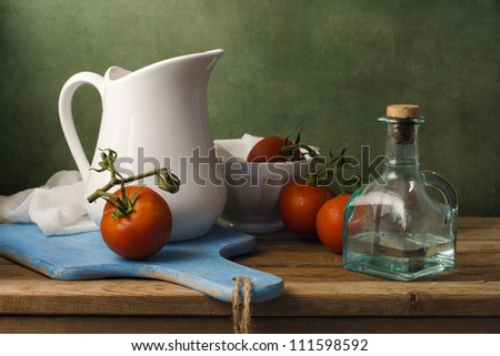 Still life with tomatoes and white jug. Arrangement on wooden table. - stock photo