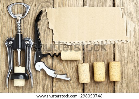 Still life with two cork-screws, wine corks and cardboard for text - stock photo