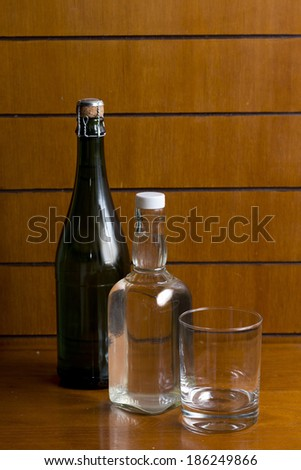 still life with various bottles of alcohol on wood background - stock photo