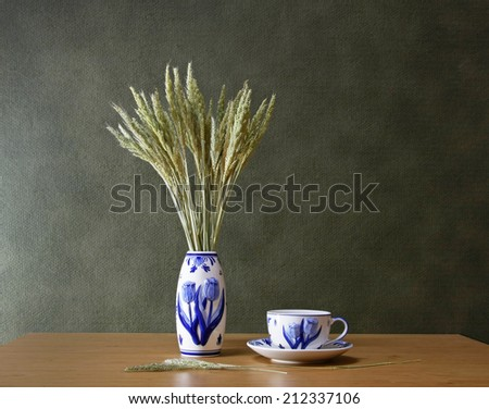 Still life with vase of dry grass flower and tea cup on wooden table.