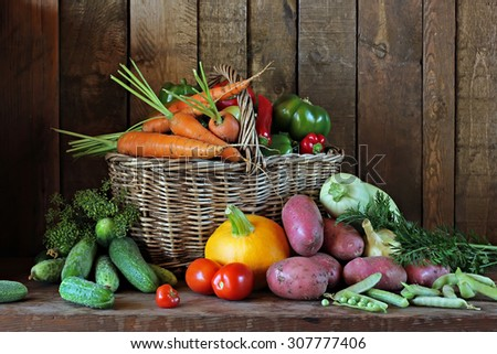Still life with vegetables: tomato, carrots, pepper, potatoes, garlic, cucumber, pumpkin, fennel, peas. Vegetables in a basket. - stock photo