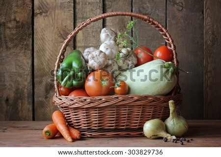 Still life with vegetables: vegetable marrow, tomato, pepper, fennel, carrots, onions, garlic. Vegetables in a basket. Ingredients for preparation of marrow caviar. - stock photo