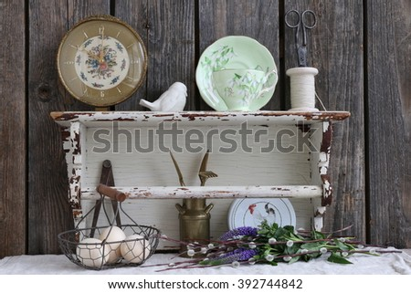Still life with very old wooden white shelf, clock, porcelain bird, garden tools, eggs in the vintage metal basket, tea set,bouquet fresh flowers - stock photo