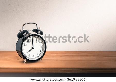 Still Life with vintage alarm clock on wood shelf  ( alarm clock show 8 o`clock ) - stock photo