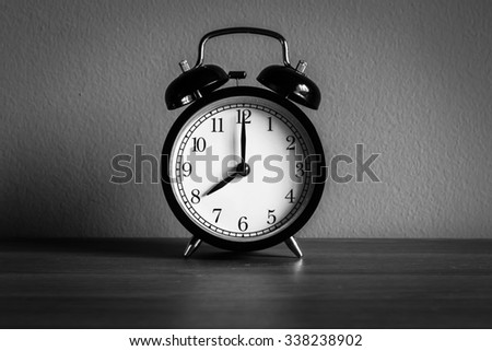 Still life with vintage alarm clock on wood table ( alarm clock show 8 o`clock ) , black and white tone - stock photo