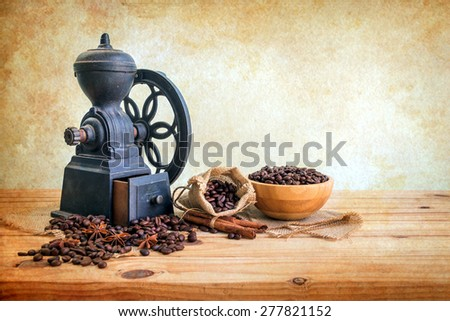 Still life with vintage coffee grinder and coffee beans on wooden table over grunge background - stock photo