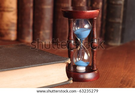 Still life with vintage hour glass and old books - stock photo