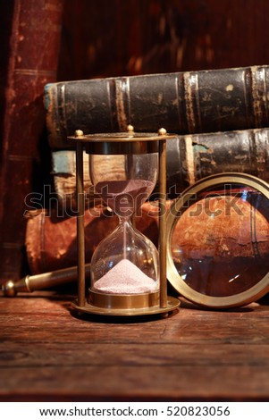 Still life with vintage hourglass near magnifying glass against old books