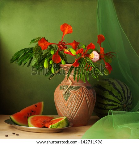 Still life with water melon and red flowers over green background - stock photo