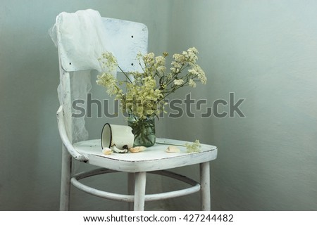 still life with white flowers, a cup on a white chair