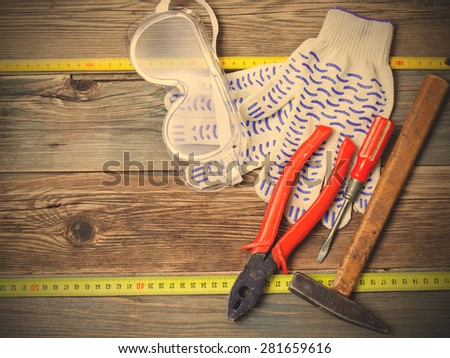 still life with working tools. Old hammer, pliers, screwdriver, tape measure, gloves and safety glasses on old textured boards bench. instagram image filter retro style - stock photo