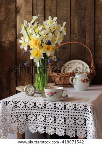 Still life with yellow daffodils in vase on table with white tablecloth with lace, old crockery and retro alarm clock in rustic style on the background of boards. The vertical frame. - stock photo