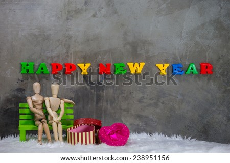 Still life, Wooden puppet men women sit on chairs, with message happy new year, and a gift box. - stock photo