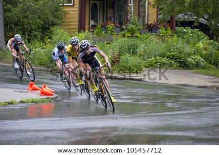 STILLWATER, MINNESOTA - JUNE 17: Pro cyclist Tom Zirbel (yellow jersey) clinches title in final stage of Nature Valley Grand Prix on a rain-soaked course at Criterium on June 17, 2012 in Stillwater - stock photo