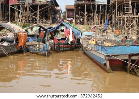 Stilt houses and boats during dry season at the Kompong Kleang floating fishing village,  Cambodia - stock photo