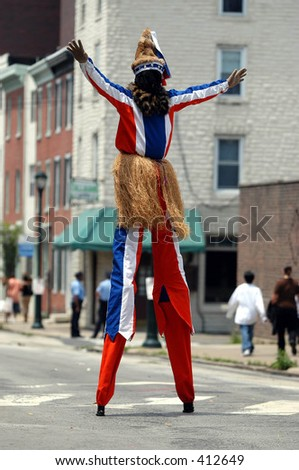 Stilt walker performing during ceremony - stock photo