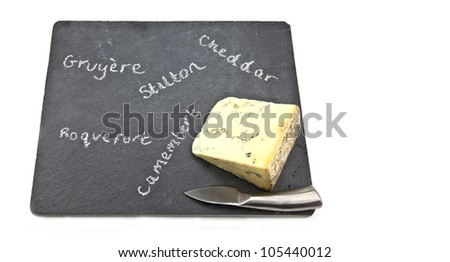 Stilton cheese on slate cheeseboard with knife with whitebackground. - stock photo