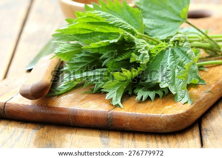 stinging nettle on a cutting board - stock photo