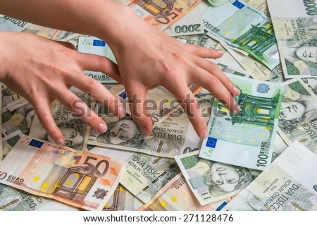 Stingy hands takes czech and euro money - stock photo