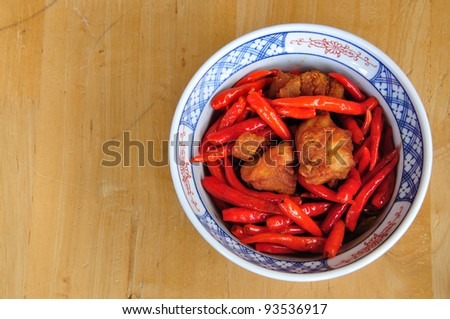 Stir fried chicken and red chilli in bowl on wood table - stock photo