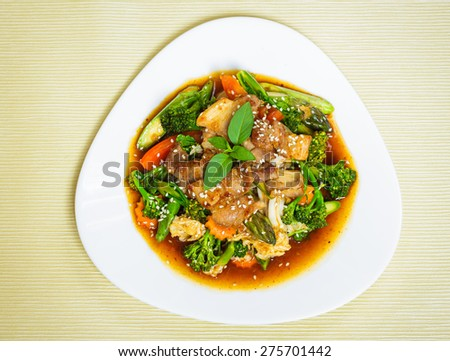 Stir fried meat and vegetable with sesame seeds in sweet chili paste and soy sauce. - stock photo