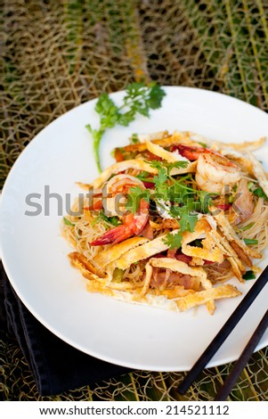 Stir fried noodles with eggs, vegetables and shrimps - stock photo
