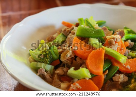 stir fried vegetables with pork in white dish./Fried vegetables.
