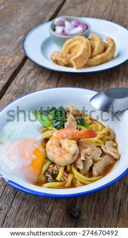 Stir fried yellow noodles with seafood , pork and soft-boiled egg  , local folk south thai style