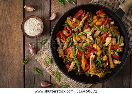 Stir fry chicken, sweet peppers and green beans. Top view - stock photo