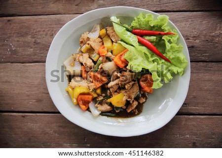 Stir fry chicken with black pepper on wood background