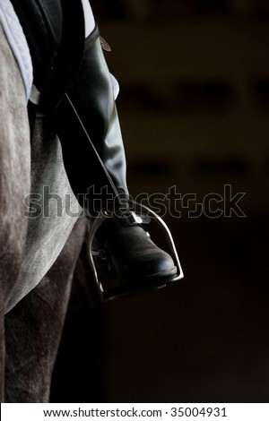 Stirrup and human leg in riding boots - stock photo