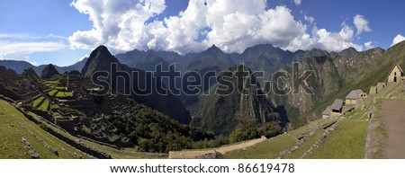 Stitched Panorama of Ruins of Machu Picchu and Huayna Picchu Peak with Andes Mountain Range and Blue Cloudy Sky in the Background - stock photo