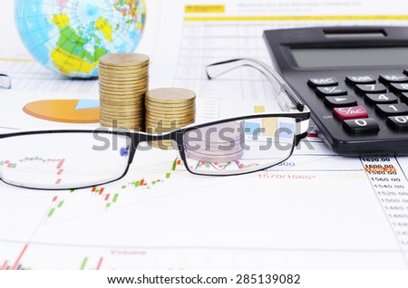 Stock chart concept with eyeglasses and coins stack and calculator