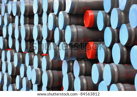 Stock gray plastic pipes with red and blue caps - stock photo