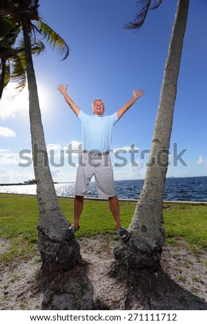 Stock image of a happy man posing between two palm trees - stock photo