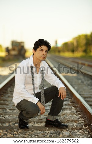 Stock image of a man posing on railroad tracks